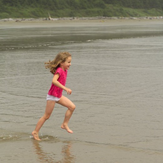 Young blond girl running on beach, Pacific Rim Park, Vancouver Island, Canada : Stock Photo