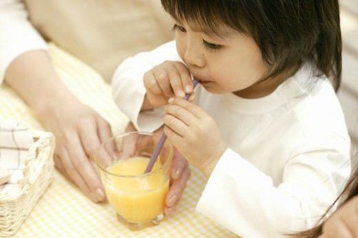 Stock Photo: 4029R-20568 A small boy drinking juice with the help of a straw