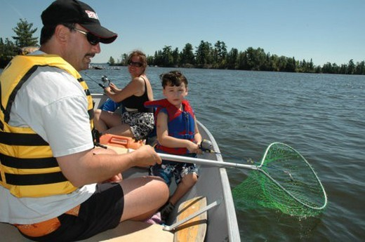Family fishing in a boat : Stock Photo