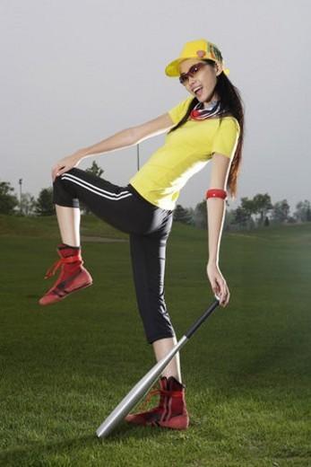 A posing young woman and baseball bat : Stock Photo