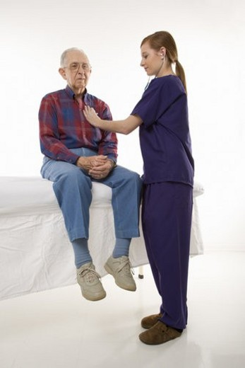 Mid-adult Caucasian female in scrubs listening to elderly Caucasian male s heart beat. : Stock Photo
