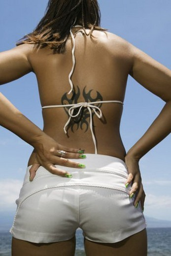Rear view of multi ethnic young adult woman on beach with hands on hips and tattoo. : Stock Photo