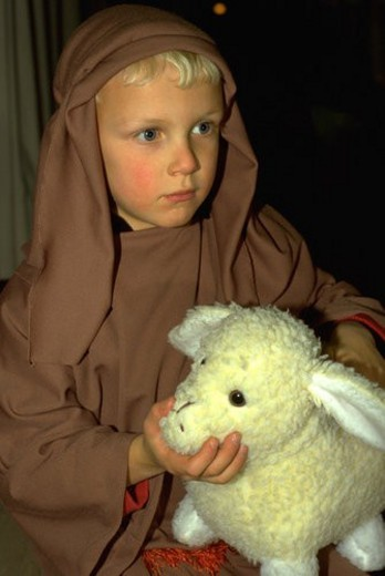 Stock Photo: 4029R-210115 Shepherd age 7 holding stuffed lamb at Christmas pageant