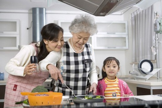 Grandmother,mother and daughter cooking in kitchen : Stock Photo