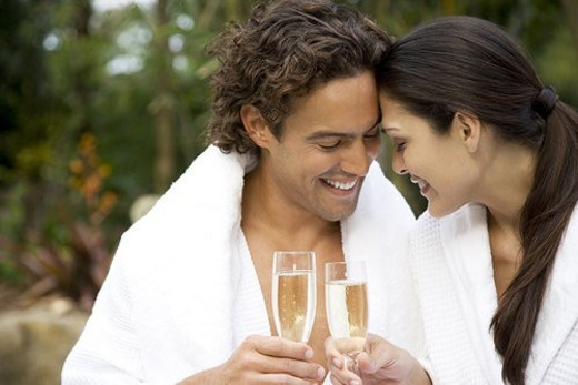 Smiling couple celebrating with champagne in a tropical garden : Stock Photo