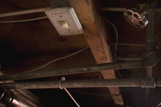 a furnace switch, valve and pipes in the ceiling : Stock Photo