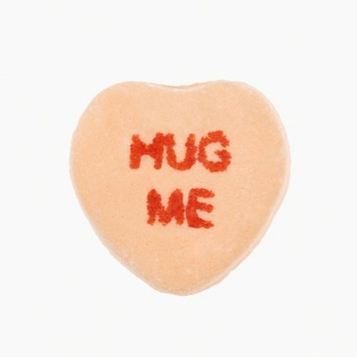 Stock Photo: 4029R-212712 Orange candy heart that reads hug me against white background.