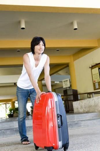 Young man carrying suitcase, smiling, Saipan, USA : Stock Photo