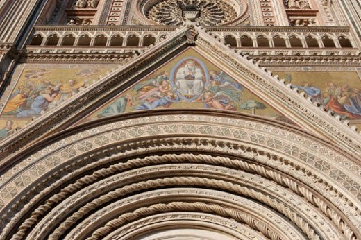 Closeup of ornate decorative spiral stonework of arch and architrave over central doorway of Orvieto Duomo, with mosaics depicting Coronation of the Virgin and other Biblical scenes on each side : Stock Photo
