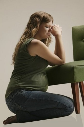 Side view of a pensive pregnant woman sitting by chair : Stock Photo
