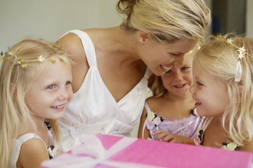 Stock Photo: 4029R-217707 Triplets with mother, birthday present in foreground