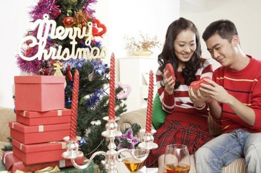 Young lovers openning gifts near Christmas tree : Stock Photo