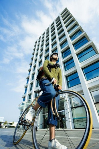 Stock Photo: 4029R-218204 The Messenger On A Bicycle In Front Of A Building