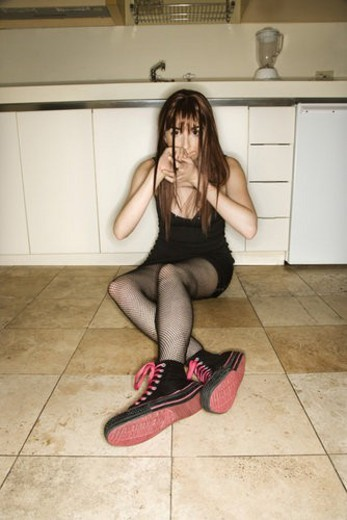 Pretty Caucasian young woman sitting on kitchen floor holding hands over mouth. : Stock Photo