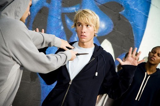 Confrontation between two young men and a group of friends in front of a graffiti covered wall : Stock Photo