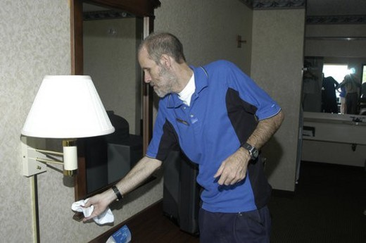 A man dusting in a hotel room. : Stock Photo