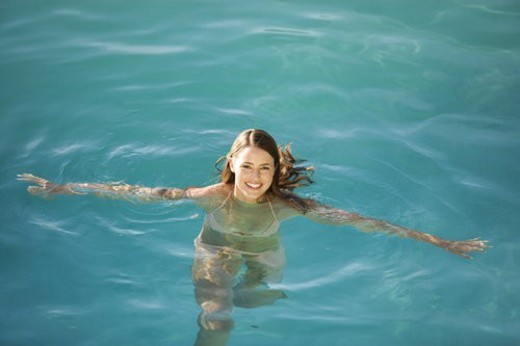 Stock Photo: 4029R-224257 A young woman swimming in a pool