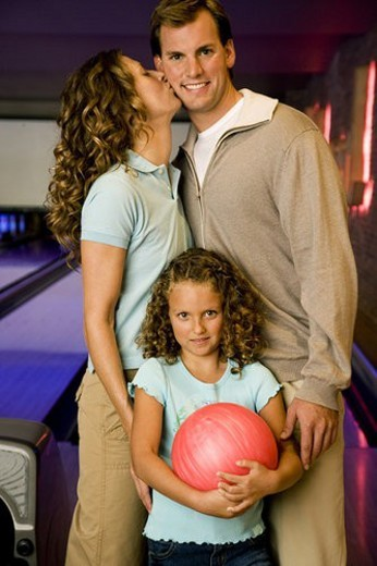 Family in a bowling alley, daughter holding a red bowling ball : Stock Photo