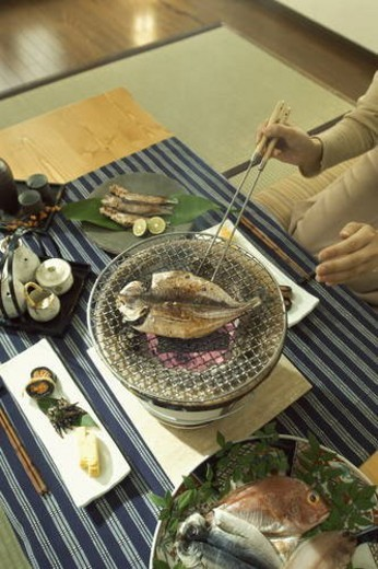 Fish being cooked on charcoal brazier : Stock Photo