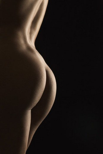 Stock Photo: 4029R-225722 Side view of nude Hispanic mid adult female back and buttocks.