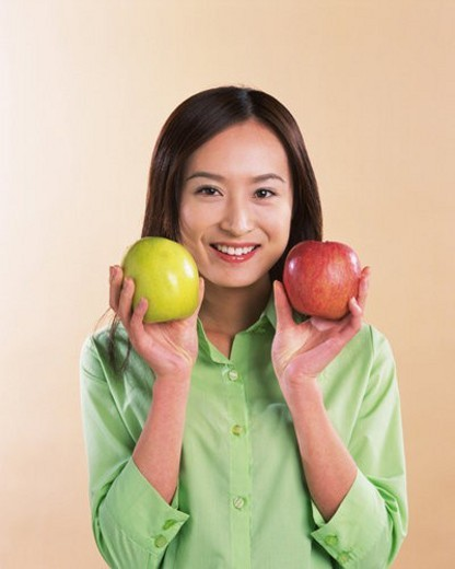 A Woman Holding Apple, Smiling, Looking at Camera, Front View : Stock Photo