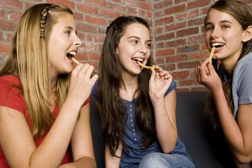 Three teenage girls eating chips : Stock Photo