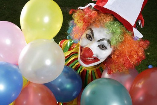 Stock Photo: 4029R-228468 Clown holding balloons, smiling