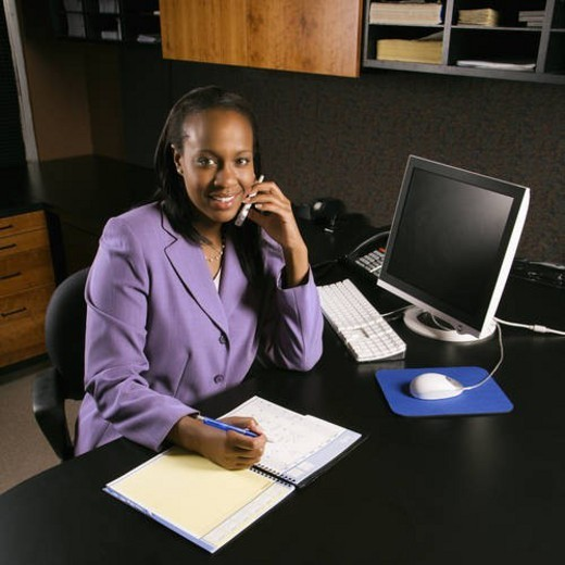 Stock Photo: 4029R-229132 African-American young adult business woman talking on cell phone and writing in planner in office smiling and looking at viewer.