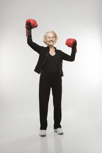 Caucasian senior woman wearing boxing gloves raised in the air. : Stock Photo