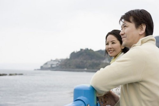 Mature couple looking at the sea, smiling, side view : Stock Photo