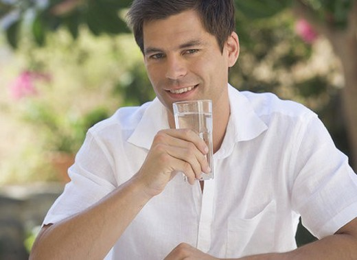 A man drinking a glass of water : Stock Photo