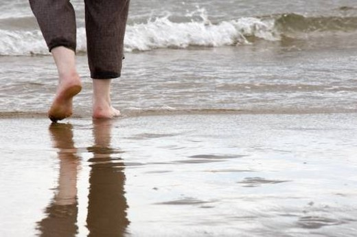 Person walking barefoot on the beach : Stock Photo