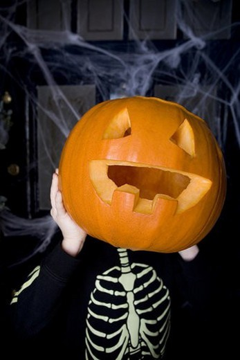 Stock Photo: 4029R-234360 Child in a skeleton costume at a Hallowe en party, holding a pumpkin with a carved face