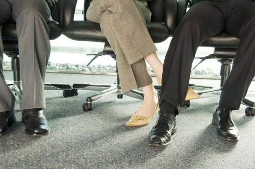 Two colleagues playing footsie : Stock Photo