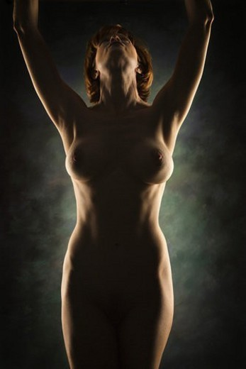 Nude Caucasian woman looking up with arms raised over head. : Stock Photo
