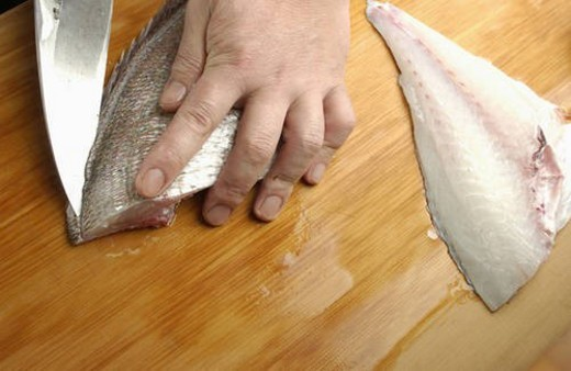 Stock Photo: 4029R-235388 Chef cutting sea bream, close up