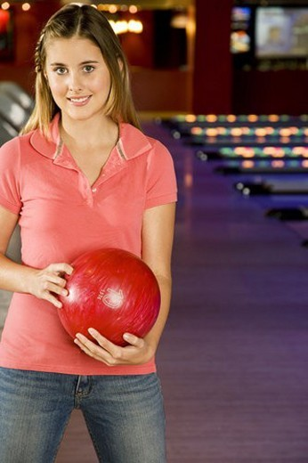 Teenage girl in bowling alley holding a red bowling ball : Stock Photo