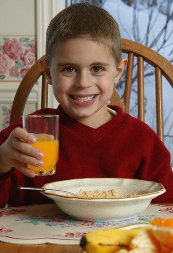 Stock Photo: 4029R-236735 Young boy with food at breakfast table