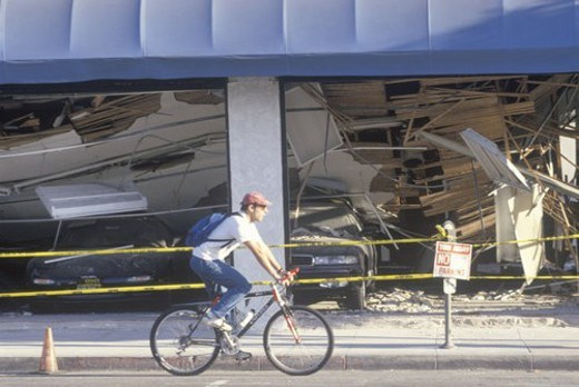 A cyclist riding past a destroyed car dealership after earthquake : Stock Photo