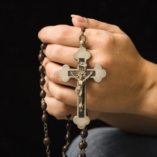 Woman s hands holding rosary with crucifix. : Stock Photo