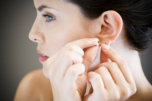 Woman putting in earrings : Stock Photo