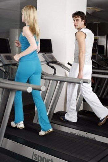 Stock Photo: 4029R-240069 Young woman and man on treadmill