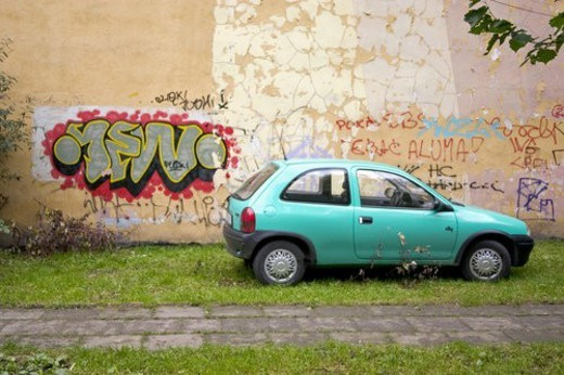 Graffiti on wall of building next to a turquoise car : Stock Photo