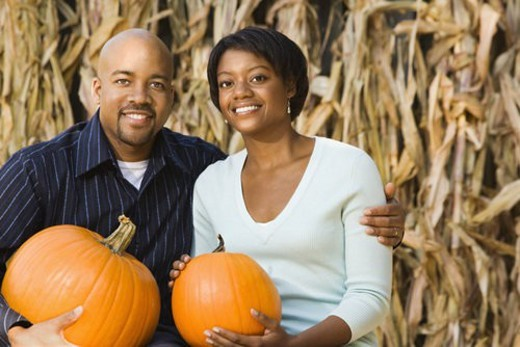 Stock Photo: 4029R-243380 Happy smiling couple sitting on hay bales and holding pumpkins at outdoor market.