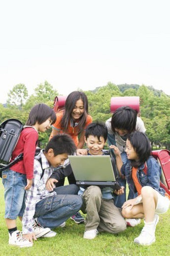 Stock Photo: 4029R-243544 Group of schoolchildren looking at a laptop