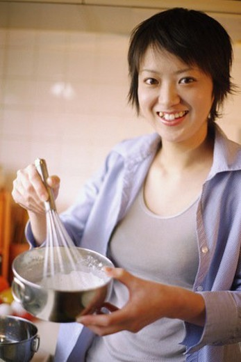 Young woman stirring mixture in a bowl, portrait : Stock Photo