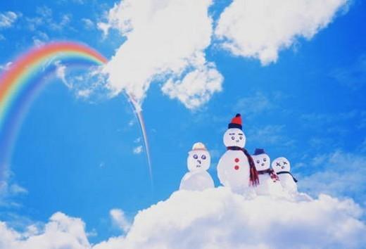 A family of snowmen on a cloud under a rainbow : Stock Photo