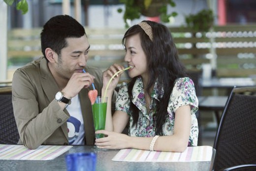 Young lovers sharing juice with straw : Stock Photo
