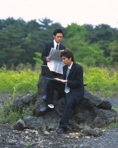 Stock Photo: 4029R-246584 Image of Two Businessmen Sitting on a Rock, the One working at his Laptop, the Other One Reading a Newspaper, Front View, Side View