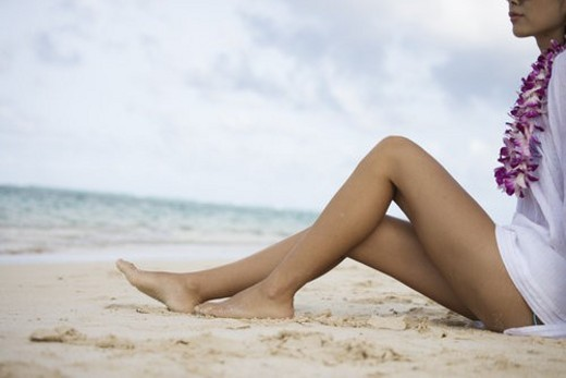 Low section of a woman sitting at beach : Stock Photo
